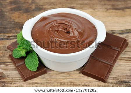 Chocolate cream with chocolate segments on wooden tables
