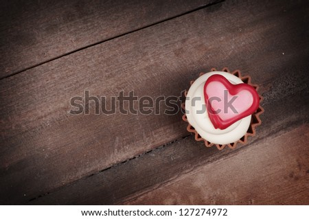 chocolate cupcake bonbon with heart on a wooden background