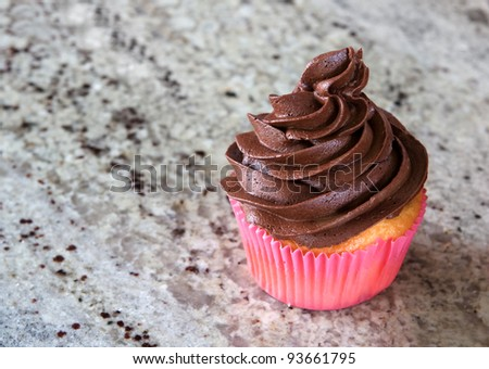 chocolate cupcake - pink wrapper - on kitchen countertop - stock photo