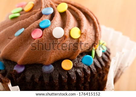 Chocolate Cupcake - This is a shot of a delicious cupcake covered in sprinkles sitting on a wooden table top. Shot with a shallow depth of field. - stock photo