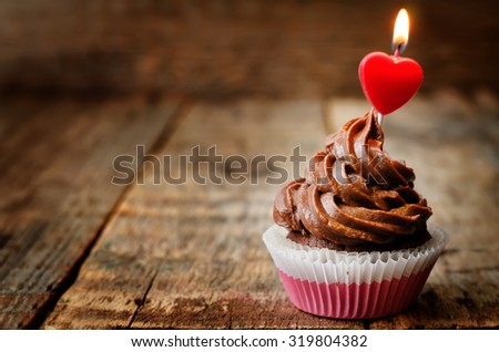 chocolate cupcake with a candle in the shape of a heart. toning. selective focus - stock photo