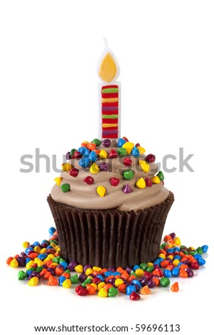 Chocolate cupcake with a fancy candle, topped with colorful sprinkles.  Isolated on white. - stock photo