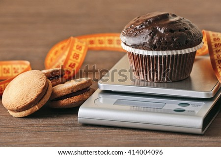 Chocolate cupcake with centimeter and digital kitchen scales on wooden table - stock photo