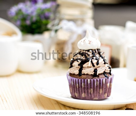 Chocolate Cupcake with chocolate frosting on the table - stock photo