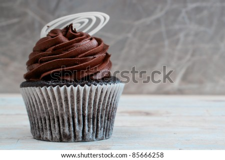 Chocolate cupcake with chocolate mousse cream icing on grunge wooden background with copy space - stock photo
