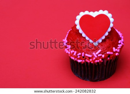 Chocolate cupcake with red heart on the top, over red background with space for the text - stock photo