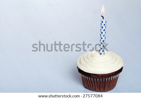 chocolate cupcake with vanilla frosting and a candle - stock photo