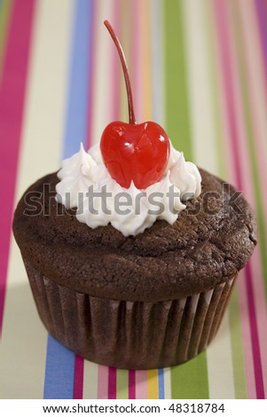 Chocolate Cupcake with Vanilla Icing and Cherry on Striped Background - stock photo