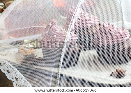 Chocolate cupcakes decorated with purple berries cream and silver sugar balls covered with food safe net umbrella