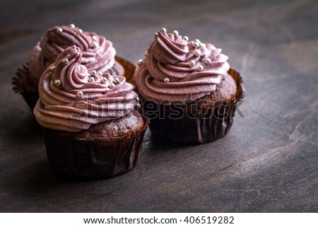 Chocolate cupcakes decorated with purple berries cream and silver sugar balls on brown wooden table - stock photo