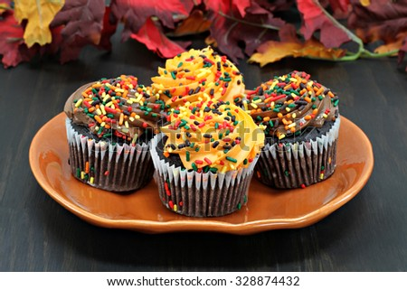 Chocolate cupcakes iced in chocolate and orange and decorated with fall sprinkles. - stock photo
