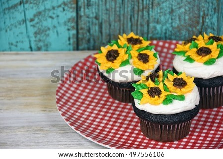 chocolate cupcakes on red and white gingham plate with sunflower icing