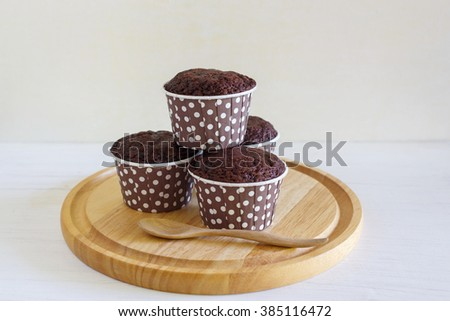 Chocolate cupcakes placed on a wooden tray and wooden spoon