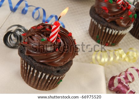 Chocolate cupcakes with birthday candles and ribbon