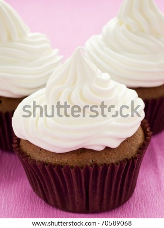 Chocolate cupcakes with whipped cream. Shallow dof. - stock photo
