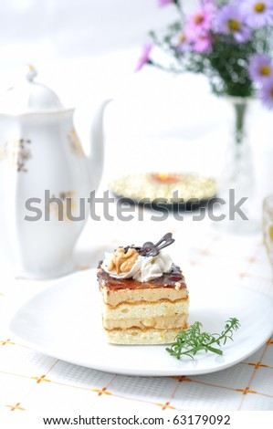 Chocolate dessert with tea, violet flowers and napkin - stock photo