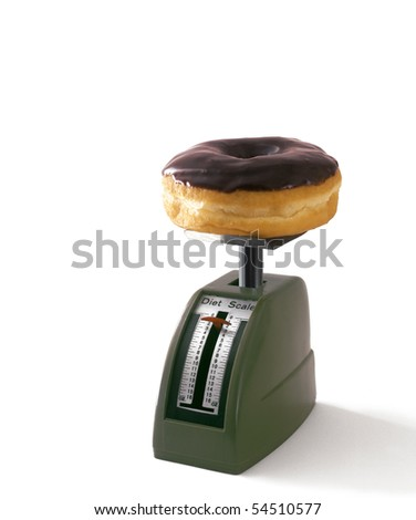 Chocolate donut on weight scale - stock photo