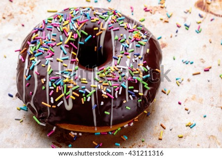 chocolate donut with sprinkles on steel plate - stock photo