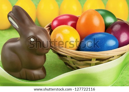 Chocolate Easter bunny and painted eggs in a basket, with light green and yellow background - stock photo