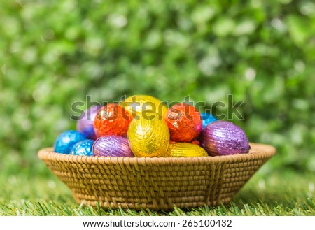 Chocolate Easter Eggs in Basket over Green grass background