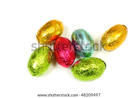 Chocolate eggs in colorful foil isolated over white