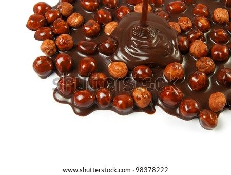 Chocolate flows on nuts. Tasty look - abstract food background - stock photo