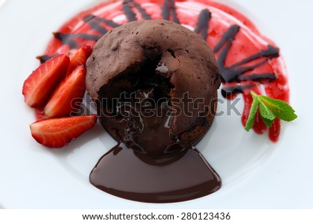 Chocolate fondant with strawberries on white plate, closeup - stock photo