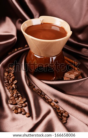 Chocolate fondue, on brown background