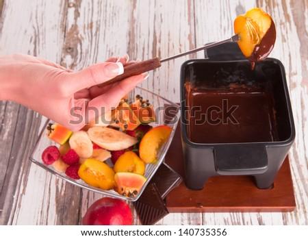 Chocolate fondue with fresh fruits on wood - stock photo