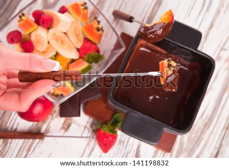 Chocolate fondue with fresh fruits on wood