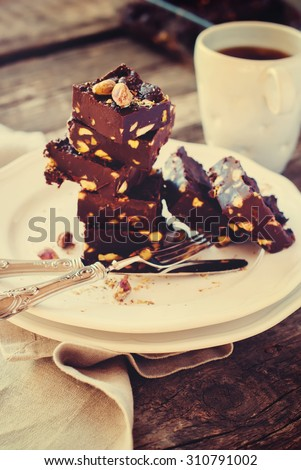 Chocolate Fudge with Pistachios on White Plate, Homemade Food, rustic style, toned - stock photo