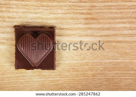 Chocolate heart on wooden texture - stock photo
