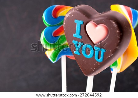 """Chocolate heart with """"I love you""""  inscription and few colorful lollipops. - stock photo"""