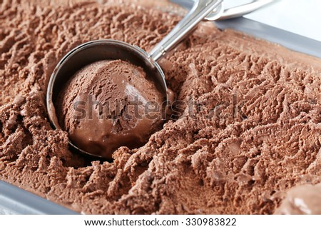 Chocolate ice cream scooped out from container - stock photo