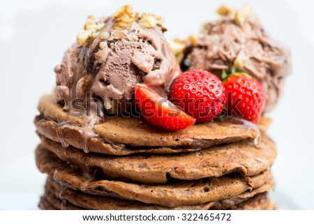 Chocolate Ice Cream Scoops on the Stack of Pancakes with Agave Syrup and Strawberries, selective focus, shallow DOF - stock photo