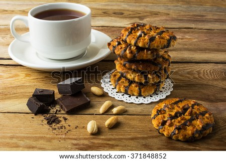 Chocolate icing cookies with peanuts and cup of tea on a rustic wooden table. Breakfast biscuits and tea. Cookies. Pastry. Biscuits. Homemade cookies. Cookie. Tea. Tea cup     - stock photo
