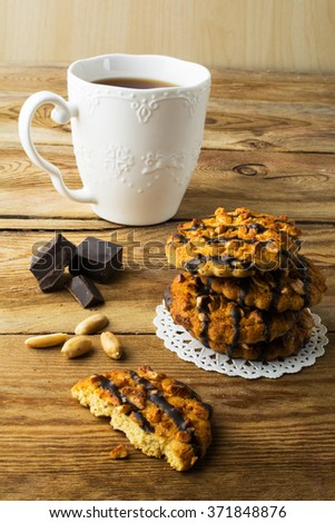 Chocolate icing cookies with peanuts and tea on a rustic wooden table, vertical. Breakfast biscuits and tea. Cookies. Pastry. Biscuits. Homemade cookies. Cookie. Tea. Tea cup   - stock photo