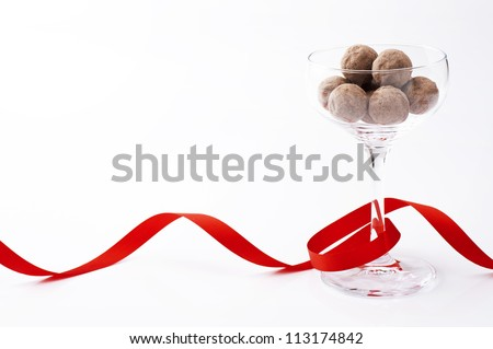 Chocolate in glass with red ribbon, white background