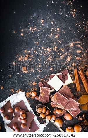 Chocolate in plates and spices in the spoons on black table - stock photo