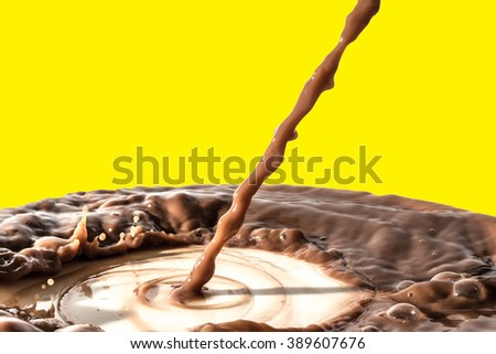 Chocolate liquid splash, pouring stream jet of chocolate, cocoa, isolated on yellow background - stock photo