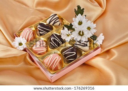 chocolate marchpane hearts candies  with  chrysanthemum daisy on golden silk textured cloth background  - stock photo