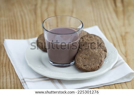 Chocolate Milk and cookies on wooden table - stock photo