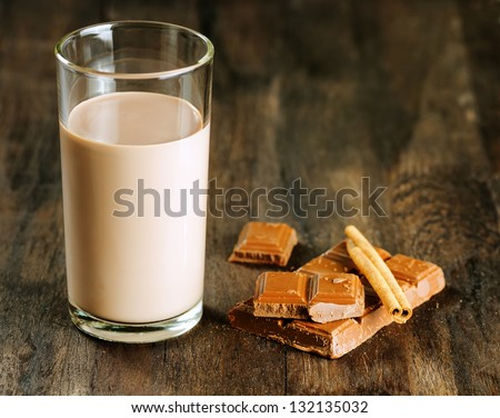 Chocolate milk with chocolate and cinnamon on dark wooden table. - stock photo