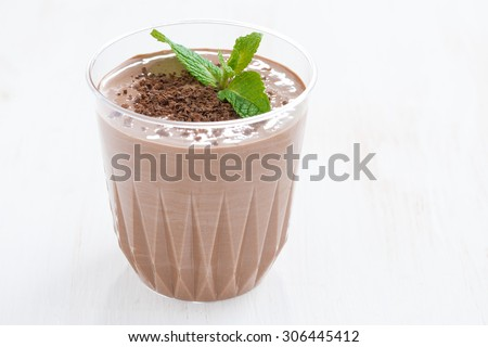 chocolate milkshake in a glass on white wooden background, close-up - stock photo