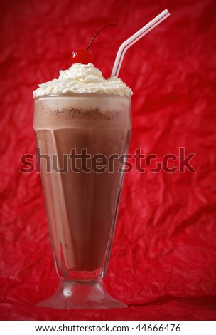 chocolate milkshake with whipped cream and cherry on the top. Focus on the cherry. Red background. - stock photo