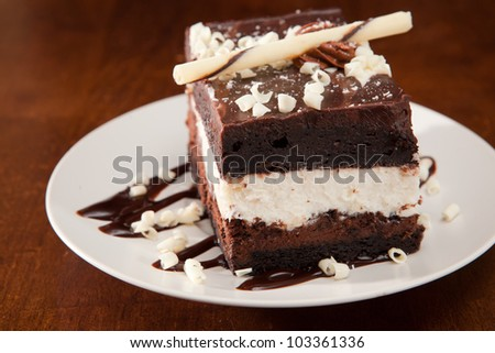 Chocolate mousse cake with white creamy layer on a white plate, on a wooden table, garnished with white chocolate. - stock photo