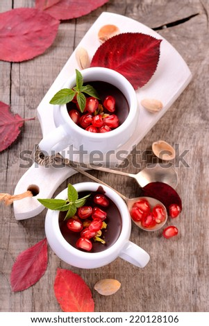 chocolate mousse in a white ceramic cup with pomegranate and mint on a wooden table with bright autumn fallen leaves - stock photo