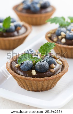 chocolate mousse with blueberries and mint in tartlets, vertical, close-up - stock photo