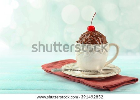Chocolate mug cake with cream and cherry on napkin on table - stock photo