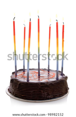 Chocolate orange cake with rainbow candles, isolated on white background.